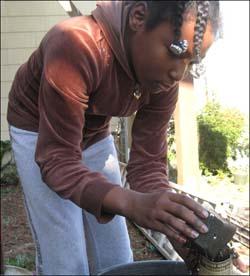Alyssa fills her paper pot with soil