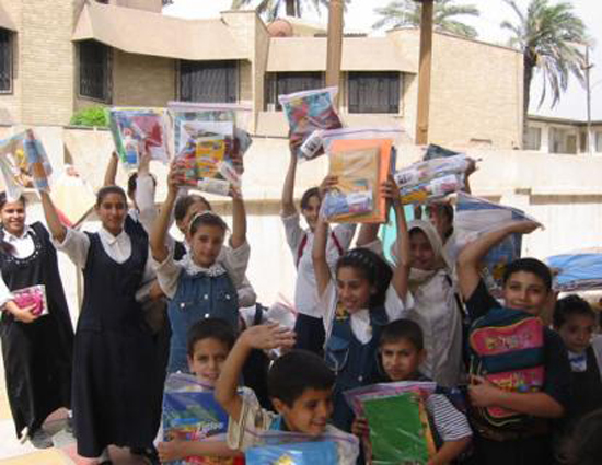 Iraqi school children showing off their School in a Backpack Kits from Lil' MDGs.
